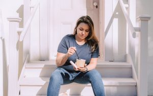 Woman sitting and eating a meal as part of her Ketogenic diet plan to address her autoimmune disease